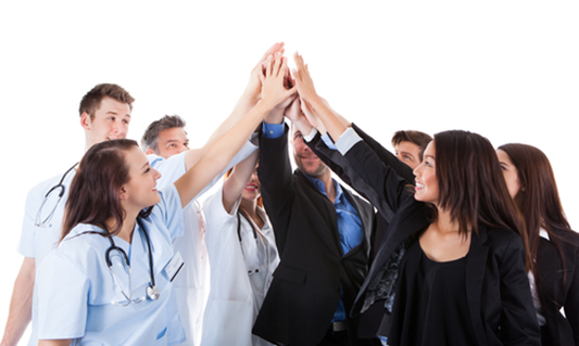 people in suits and scrubs doing a group high-five